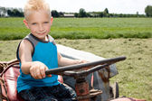 Little boy is steering a tracor. — Stock Photo