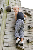 Young boy is climbing a wall. — Stock Photo
