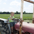 Young man at a farm vehicle — Stock Photo