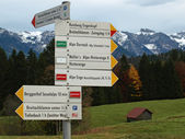 Sign with directions to different restaurants in the alps — Stock Photo