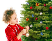 Little girl dresses up a christmas-tree — Stock Photo