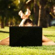 Barefoot woman on the grass hiding behind her laptop — Stock Photo #3969290