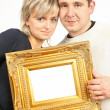 Woman and man holding gold frame - Stock Photo