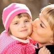 Mother kissing her little girl — Stock Photo