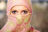 Muslim woman hidden behind a scarf — Stock Photo
