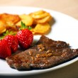 Beef steak with sliced potatoes and strawberries — Stock Photo #5088370