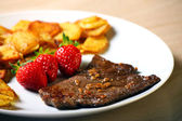 Beef steak with sliced potatoes and strawberries — Stock Photo