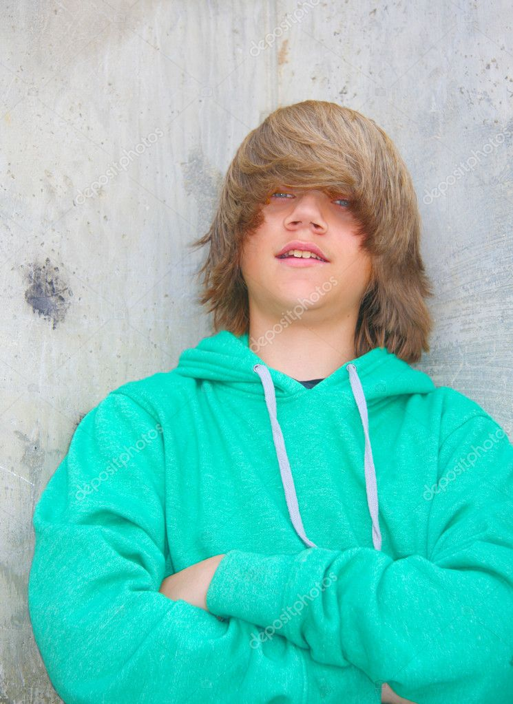 Cute teen boy with shaggy blond hair and wearing a green sweatshirt standing against a cement wall with graffiti. — Stock Photo #3945588