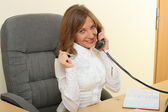 Business woman speeking over the phone and computer — Stock Photo