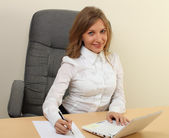 Businesswoman writing with laptop in office — Stock Photo