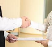 Man and woman shaking hands in office and giving papers — Stock Photo