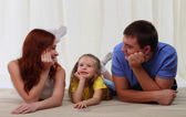 Happy family laying on floor at home — Stock Photo