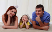 Happy family laying on floor at home — Stockfoto