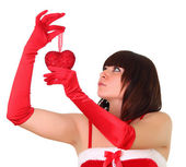 Brunette girl in santa dress holding a heart chistmas decoration — Stockfoto