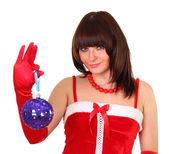 Brunette girl in santa dress holding a heart chistmas decoration — Stock Photo