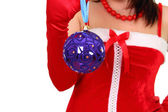 Brunette girl in santa dress holding a heart chistmas decoration — Stock Photo