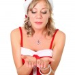 Girl in santa dress blowing something on her hand isolated over a white bac — Stock Photo