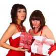 Two pretty brunette girls in santdress holding presents — Stock Photo #4477399
