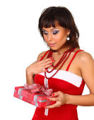 Brunette girl in santa dress holding present and looking on it with amaze — Stock Photo