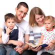 Happy family reading a book on sofa — Stock Photo #4618352