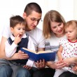Happy family reading a book on sofa — Stock Photo