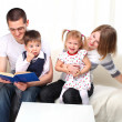 Happy family reading book on sofa — Stock Photo #4618401
