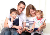 Happy family reading a book on sofa — Stockfoto