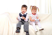Little boy and girl playing tv game on sofa — Stockfoto