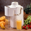Juicer with glass and fruit — Stock Photo