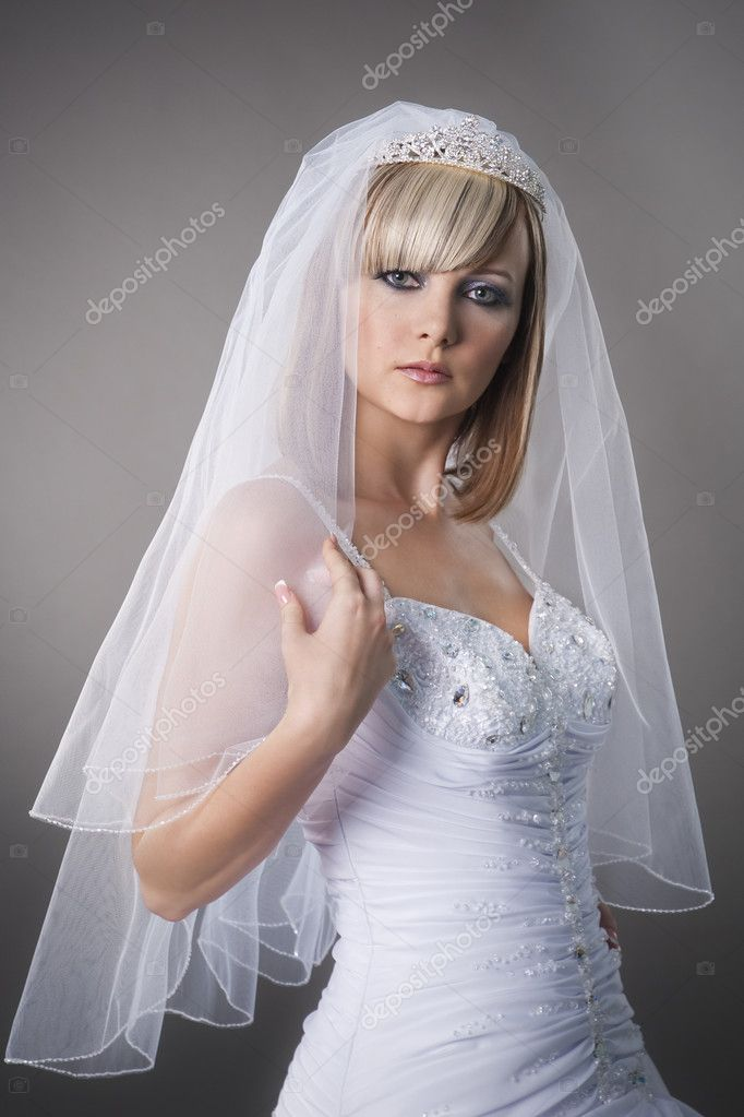 Positive beautiful bride in the wedding gown and veil at the studio — Stock Photo #3986377