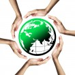 Green planet (Earth) surrounded by hands — Stock Photo