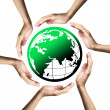 Green planet (Earth) surrounded by hands - Stock Photo
