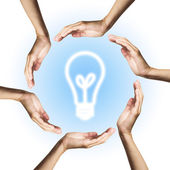 Glowing light bulb surrounded by hands — Stock Photo