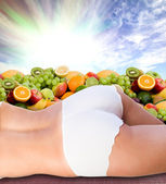 Woman body over fresh fruits and sunny sky — Stock Photo