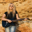 Beautiful blonde with a guitar on rock background — Stock Photo