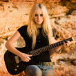The beautiful blonde with a guitar on rock background — Stock Photo