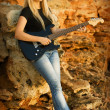 The beautiful blonde with a guitar on rock background — Stock Photo #3997246