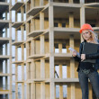 Stock Photo: Young girl in helmet before building