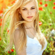 Stock Photo: Young girl with long hair in poppies field