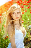 Young girl with long hair in poppies field — Stock Photo