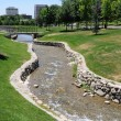 Artificial Stream Flows through Urban Park - Stock Photo