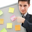 Stock Photo: Businessman showing onto the reminder board