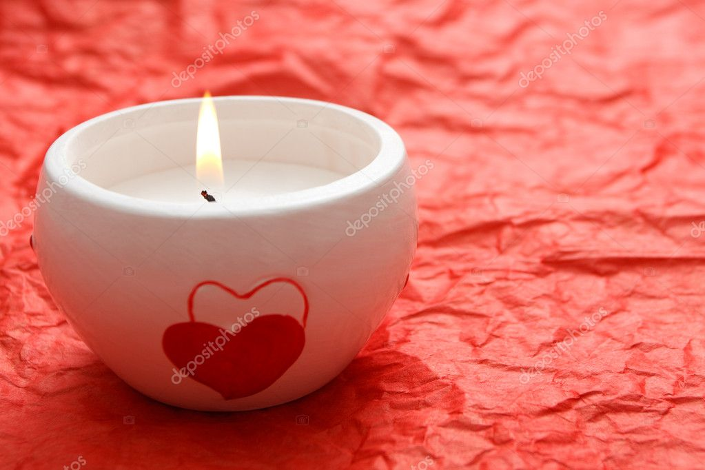 A burning white candle with hearts on it on the red background — Stock Photo #4145468
