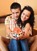Happy couple with miniature house — Stock Photo