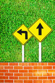 Traffic sign on brick wall and grass field — Stock Photo