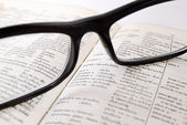 Closeup of old dictionary and glasses — Stock Photo