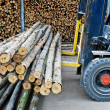 Truck loading pile of wood in logs storage - Stock Photo