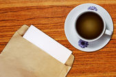 White cup of coffee and brown envelope — Stock Photo