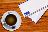 空気メール エンベロープとコーヒー カップ — ストック写真