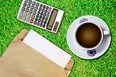 Bílý šálek kávy a hnědé obálky — Stock fotografie